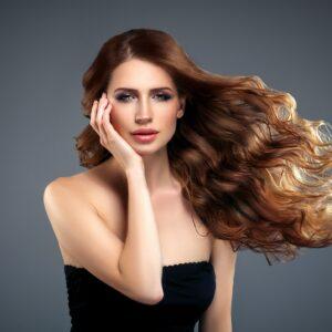 Beautiful hair woman beauty skin portrait over dark background. Long beautiful healthy hair mode